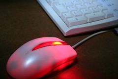 Computer Hardware. An optical mouse glowing red with keyboard in the background royalty free stock images