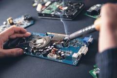 Computer hardware engineering. Engineer soldering computer motherboard stock photography