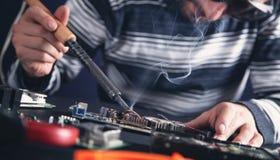 Computer hardware engineering. Engineer soldering computer motherboard stock photos