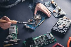 Computer hardware engineering. Engineer soldering computer motherboard royalty free stock images