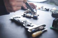 Computer hardware engineering. Engineer soldering computer motherboard stock images