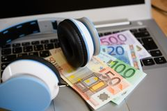 Computer with headphones and euro bank notes stock photo