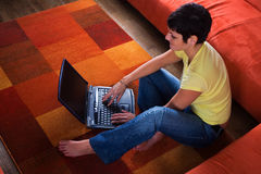 Computer at home. Young woman is using a laptop computer is her comfortable living room Royalty Free Stock Images
