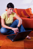 Computer at home. Young woman is using a laptop computer is her comfortable living room Stock Photography