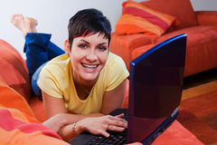 Computer at home. Young woman is using a laptop computer is her comfortable living room Stock Photos