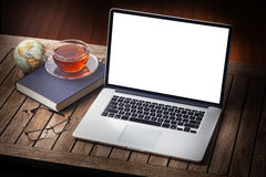 Computer Home Desk. A still-life with a laptop computer, glasses, book and cup of tea with a blank screen Royalty Free Stock Photography