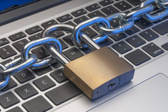 Computer internet security. Padlock and chain on keyboard to illustrate internet security Stock Photos