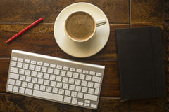 Computer keyboard, Cup of coffee, a notebook and red pencil on the table made. Royalty Free Stock Photo