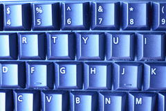 Computer keyboard detailed background. Blue toned keyboard captured close up Royalty Free Stock Photos