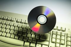 Computer keyboard and DVD disk royalty free stock photo