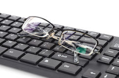 Computer keyboard and eye glasses Stock Photography