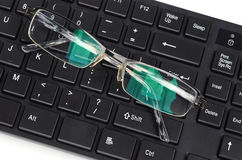 Computer keyboard and eye glasses Royalty Free Stock Image