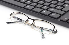 Computer keyboard and eye glasses Stock Images