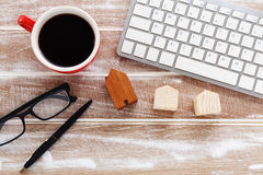 Computer keyboard with house model on wood background. Computer keyboard with house model and coffee cup on wood background stock images