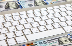 Computer keyboard lying on a  on the background of dollars Royalty Free Stock Images