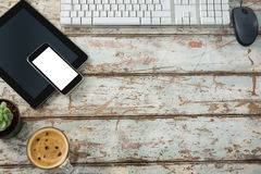 Computer keyboard, mouse, digital tablet and smartphone with coffee cup Stock Photos