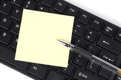 Computer keyboard and notepaper with pen Stock Photography