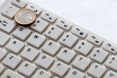 Computer keyboard and one euro coin close up on a white background. Internet business. Currency exchange stock photography
