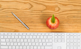 Computer keyboard with pen and apple on desktop Royalty Free Stock Photos