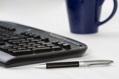 Computer keyboard, pen and coffee cup. Close-up of a desk with computer keyboard, pen and coffee cup Royalty Free Stock Photos