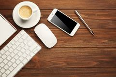 Computer keyboard, phone and cup of coffee. On wooden background stock photography