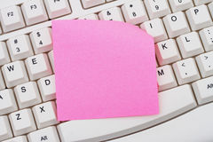 Computer Keyboard with a pink blank sticky note Royalty Free Stock Image