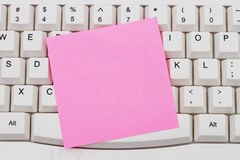 Computer Keyboard with a pink blank sticky note Stock Image