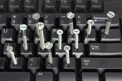 Computer Keyboard and Screws Stock Photography