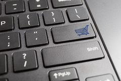 Computer keyboard with shopping cart icon. Blue shopping cart key on computer keyboard , online shopping concept Royalty Free Stock Images