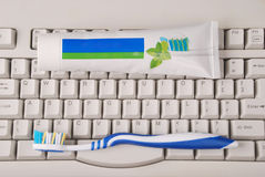 Computer keyboard, toothpaste and toothbrushes. Royalty Free Stock Photography