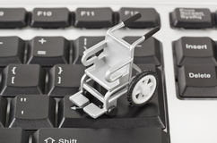 Computer keyboard and wheelchair Stock Images