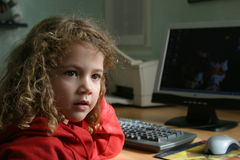 Computer kid. Little girl at the computer desk Stock Photos