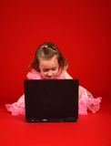 Computer kid. Young child sat on the floor using a laptop computer Stock Images