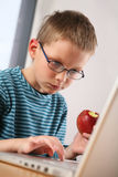 Computer kid. Eating apple Royalty Free Stock Image