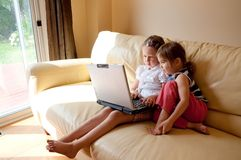 Computer Kids. Two little girls using laptop at home Royalty Free Stock Photography