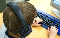Computer-Kind mit Kopfhörern Stockfotos