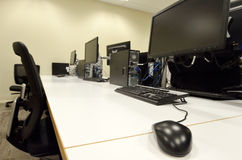 Computer lab room. With empty workstation office desk and chairs. Concept photo of business workplace Royalty Free Stock Photo
