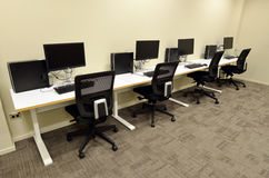 Computer lab room. With empty workstation office desk and chairs. Concept photo of business workplace Stock Photography
