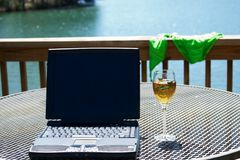 Computer at the Lake. A computer on a table with a glass of wine.  Water and bikini in the background Stock Images
