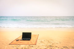 Computer laptop at the beach on tropical destination Stock Photo