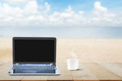 Computer laptop with black screen and hot coffee cup on wooden table top on blurred beach background Stock Photography