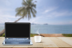 Computer laptop with black screen and hot coffee cup on wooden table top on blurred beach with coconut tree background Royalty Free Stock Images