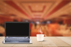 Computer laptop with black screen and hot coffee cup on wooden table top on blurred hotel lobby background Stock Images