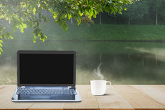 Computer laptop with black screen and hot coffee cup on wooden table top on blurred misty lake and forest background Stock Photos