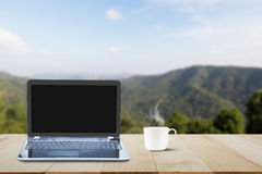 Computer laptop with black screen and hot coffee cup on wooden table top on blurred mountain background Stock Images