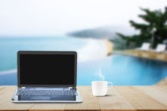Computer laptop with black screen and hot coffee cup on wooden table top on blurred pool and beach background Stock Photography