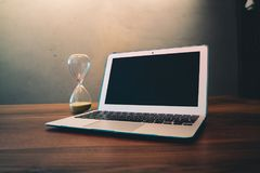 Computer Laptop Beside Hour Glass on Brown Wooden Surface Stock Images