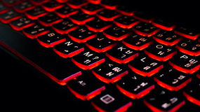 Computer laptop keyboard with red dark backlight, backlit in the dark. Concept computer keyboard background. stock photo