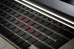 Computer laptop keyboard with the words FAKE NEWS in red letters. On black keys, selected focus, narrow depth of field Stock Photos