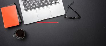 Computer laptop and mobile phone on black color office desk, banner. Modern workspace. Computer laptop and mobile phone on black color office desk, banner, top royalty free stock photography